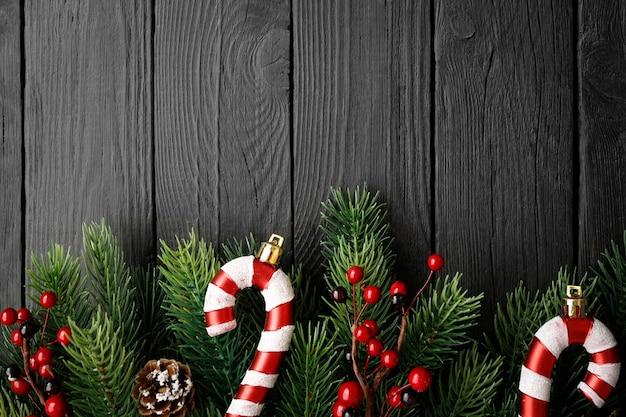 Dulces de navidad, abeto, conos y bayas sobre fondo negro de madera