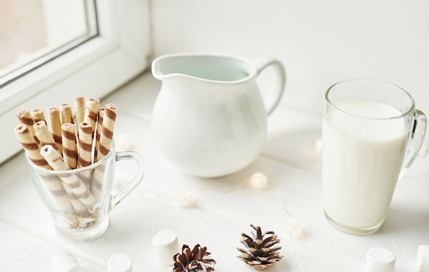 Dulces navideños y leche sobre un blanco junto a la ventana