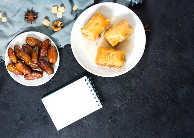 Dulces orientales con dátiles frutales y bloc de notas.