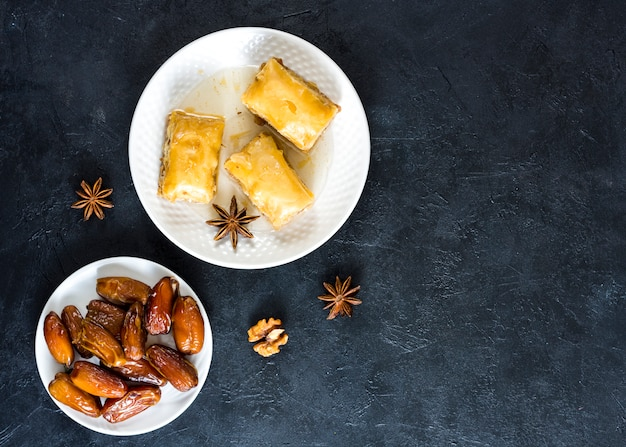 Dulces orientales con dátiles frutales en mesa negra.