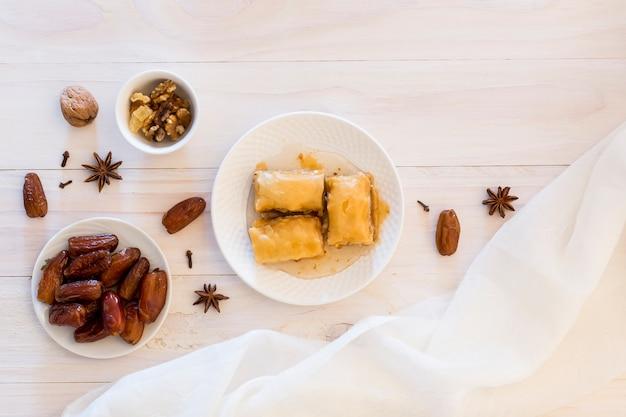 Dulces orientales con dátiles frutales y nueces en mesa.