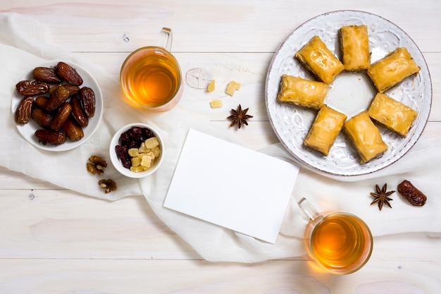 Dulces orientales con dátiles frutales y papel en blanco.