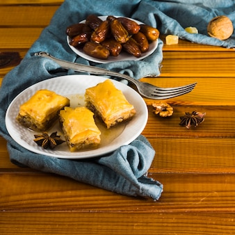 Dulces orientales con dátiles frutales en plato sobre mesa
