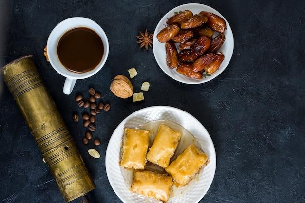 Dulces orientales con dátiles frutales y taza de café.