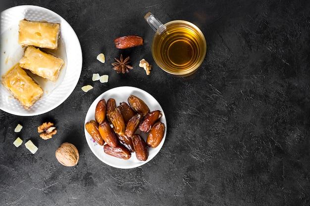 Dulces orientales con dátiles frutales y taza de té.