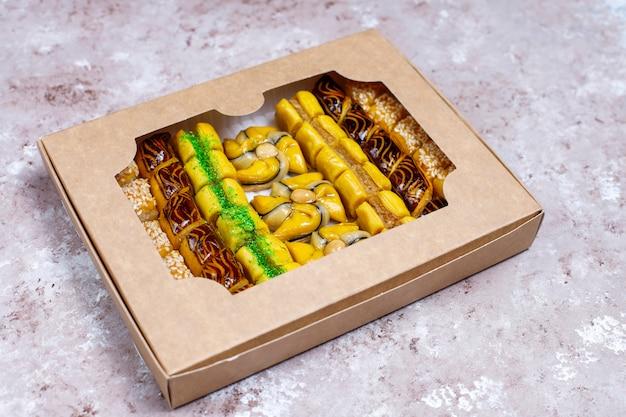 Dulces orientales tradicionales con diferentes frutos secos sobre fondo de hormigón, vista superior, espacio de copia