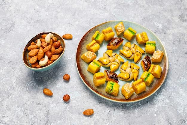 Dulces orientales tradicionales con diferentes frutos secos sobre superficie de hormigón
