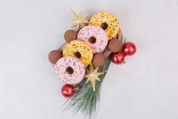 Dulces pasteles navideños con bolas sobre superficie blanca