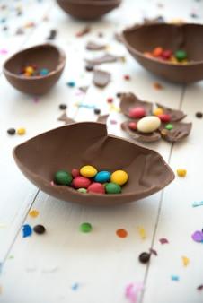 Dulces pequeños en huevo de chocolate abierto.
