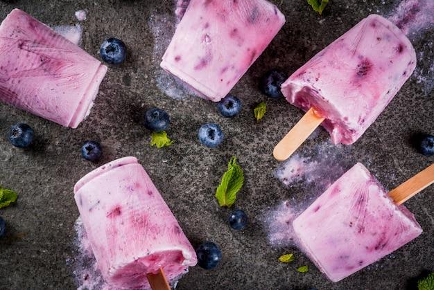 Dulces y postres de verano. comida vegana. bebidas congeladas, batidos. paletas de helado de yogur griego casero y arándanos orgánicos frescos. con menta en la mesa de piedra negra. vista superior de copyspace