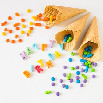 Dulces que se derraman de cono de helado de galleta en feliz cumpleaños