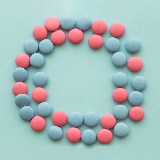 Dulces rosados y azules dispuestos en forma circular sobre el fondo coloreado
