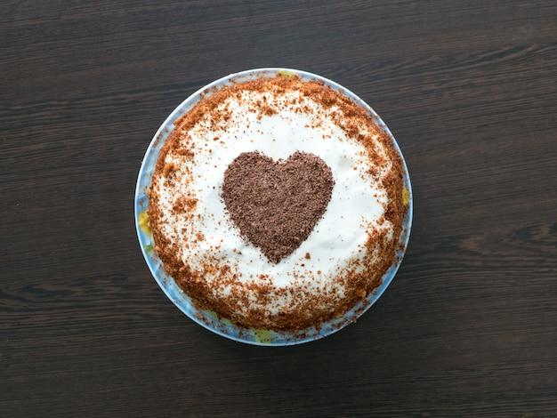 Dulces para san valentín. tarta hecha a mano con glaseado de queso crema y un corazón de chocolate. concepto de san valentín