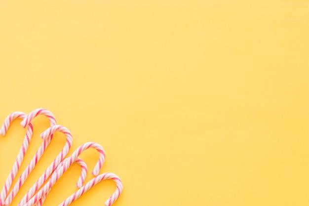 Dulces tradicionales de navidad de menta en la esquina de fondo amarillo