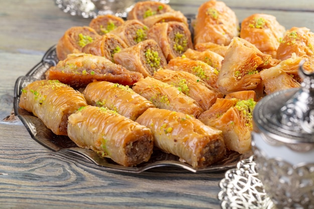 Dulces turcos baklava y bandeja oriental de metal sobre fondo de madera