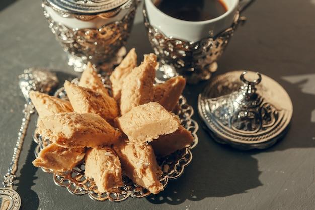 Dulces turcos con café en una mesa de madera