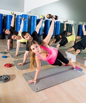 Dumbbell push up grupo de entrenamiento funcional en gimnasio.