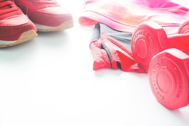 Dumbbells rojos y desgaste del deporte en fondo del fittness. ropa deportiva, moda deportiva, accesorios deportivos, equipo deportivo.