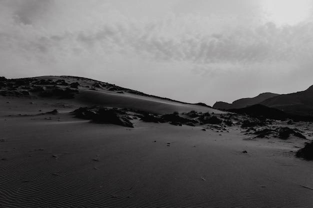 Duna de postre con cielo nublado en blanco y negro