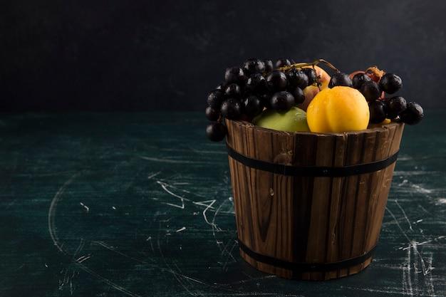 Duraznos y uvas en un balde de madera en pizarra
