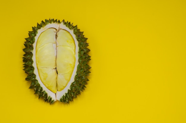 El durian fresco del corte que es rey de la fruta de tailandia aisló en fondo amarillo con el espacio para el texto.