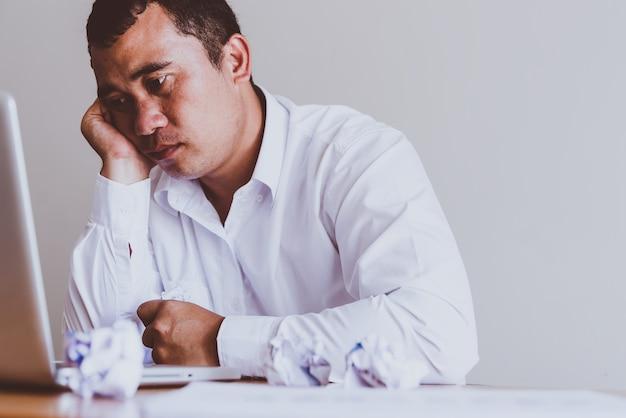 Duro pensar en el análisis en el trabajo. destacó el joven empresario asiático trabajando en su escritorio en el trabajo