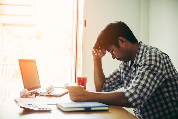 Duro pensar en el análisis en el trabajo. el hombre de negocios asiático joven está trabajando en la presión en oficina.