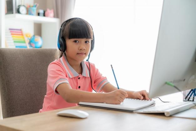 E-learning de la videoconferencia de la estudiante asiática con el profesor en la computadora en sala de estar en casa.