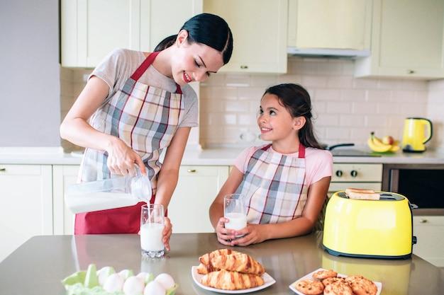 Eautiful mujer está vertiendo leche en vasos de vidrio. niña sostiene su propia taza y mira a mamá. ella sonríe. están pendientes de tiempo juntos.