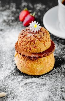 Eclair de postre francés con chocolate y una flor en la parte superior.