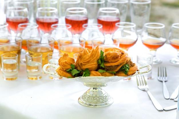 Eclairs y bebidas en una mesa de banquete.