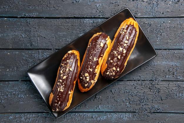 Eclairs de chocolate de vista superior cercana en placa rectangular sobre mesa de madera oscura con espacio libre