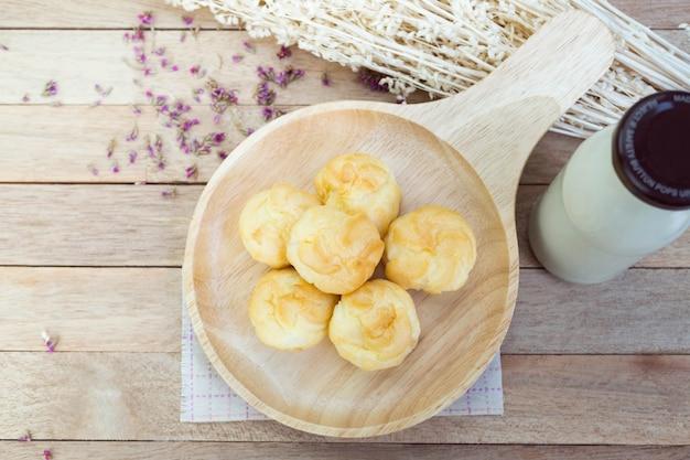 Eclairs de crema de vainilla en la mesa de madera
