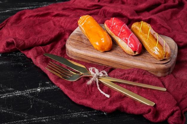 Eclairs con jarabes de colores en una bandeja de madera con cubiertos.