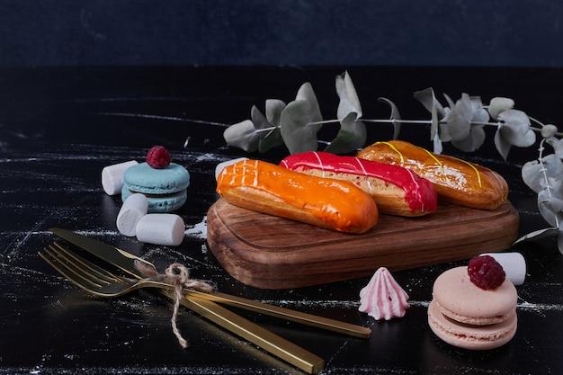 Eclairs con jarabes de colores en bandeja de madera con macarons.