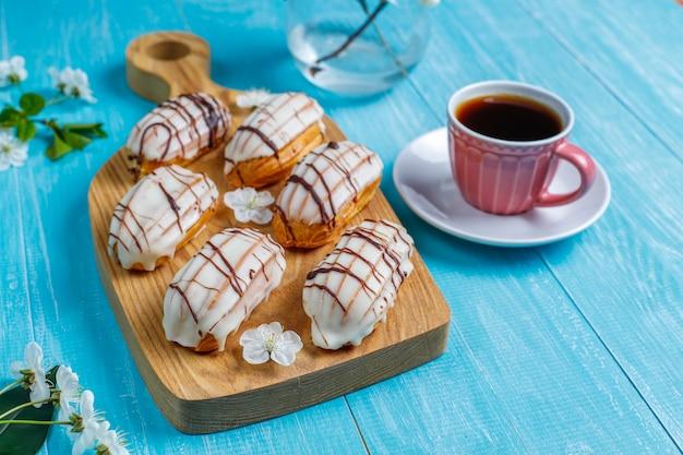 Eclairs o profiteroles con chocolate negro y chocolate blanco con natillas dentro, postre francés tradicional. vista superior.