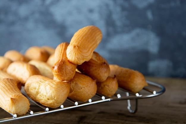 Eclairs o profiteroles preparando en una bandeja para hornear. postre tradicional francés.