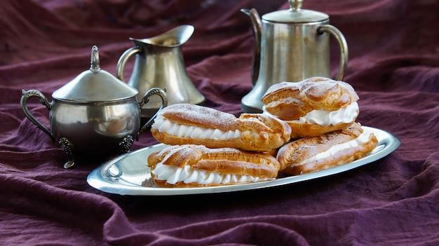 Eclairs, pastas choux rellenas con crema batida, fondo violeta oscuro, vajilla de plata