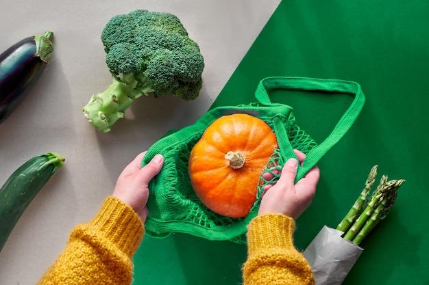 Eco amigable cero basura plana con manos sosteniendo brócoli y bolsa de cadena con calabaza naranja. vista superior de otoño o primavera con verduras en papel de dos colores, papel artesanal y verde.