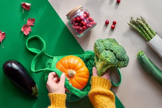 Eco amigable cero basura plana yacía con las manos sosteniendo brócoli y una bolsa de hilo con calabaza naranja vista superior con verduras y bayas de arándano en frasco de vidrio