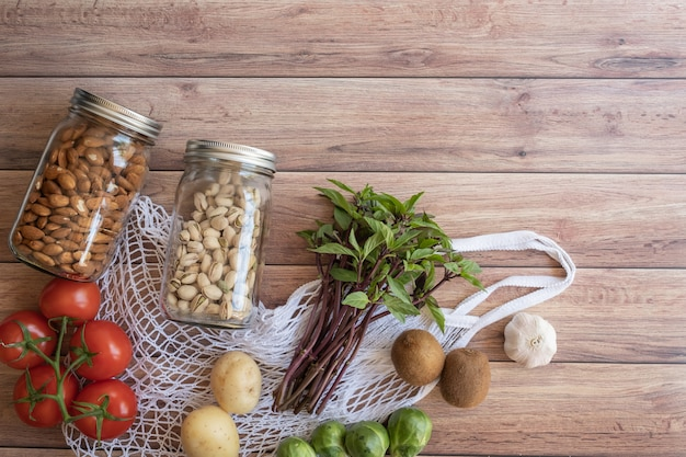 Eco bolsa neta de comida sana vegana sobre superficie de madera. compras de comestibles libres de plástico. vista superior. lay flat