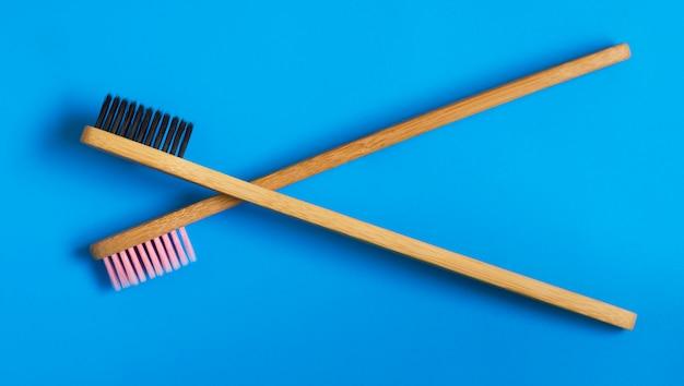 Eco cepillos de dientes de bambú natural sobre fondo azul. cero desperdicio plano pone 10