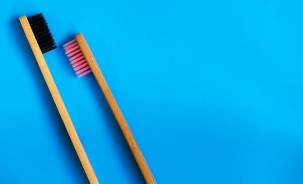 Eco cepillos de dientes de bambú natural sobre fondo azul. cero desperdicio plano pone 8