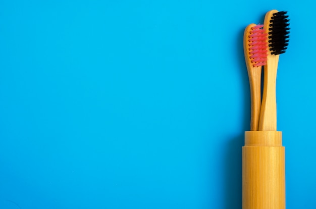 Eco cepillos de dientes de bambú natural sobre fondo azul. cero desperdicio plano puesto 13