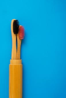 Eco cepillos de dientes de bambú natural sobre fondo azul. cero desperdicio plano puesto 15