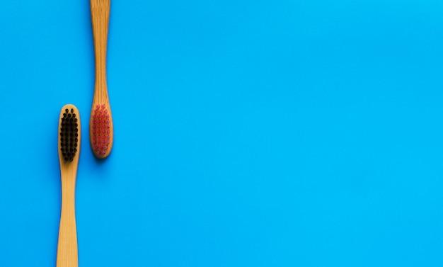 Eco cepillos de dientes de bambú natural sobre fondo azul. cero desperdicios planos. 2