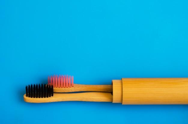 Eco cepillos de dientes de bambú natural sobre fondo azul. cero residuos plano pone 16