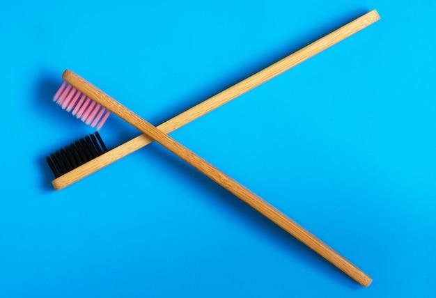 Eco cepillos de dientes de bambú natural sobre fondo azul. cero residuos plano pone 9