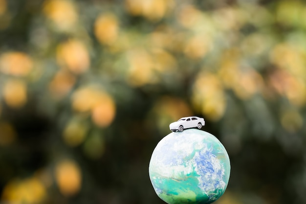 Eco salvar el medio ambiente mundial / concepto de deporte de viaje: coche de figuras en miniatura en el modelo mundial mundial, ecología respetuosa con el medio ambiente