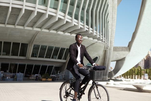 Ecológicamente consciente joven empresario europeo negro vistiendo traje negro y gafas de sol en bicicleta al café en bicicleta retro durante el almuerzo en un día soleado